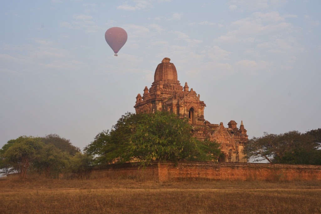 Temple and hot air balloon at sunrise in Bagan